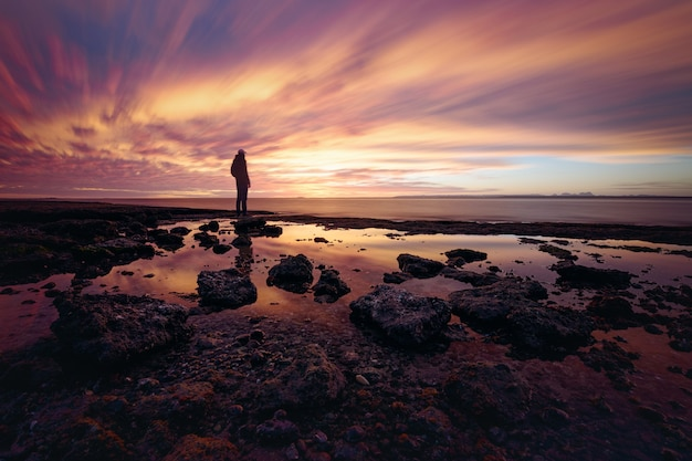 Iemand die geniet van de zonsondergang op de rotsachtige kust bij san ignacio lagoon, baja california, mexico