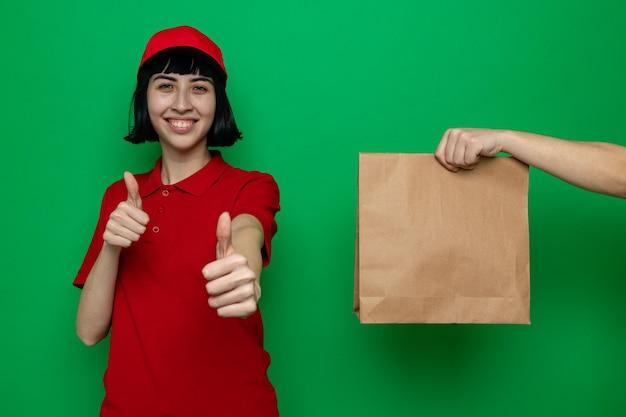 Iemand die voedselverpakkingen geeft aan een glimlachend jong kaukasisch bezorgmeisje dat omhoog duimt