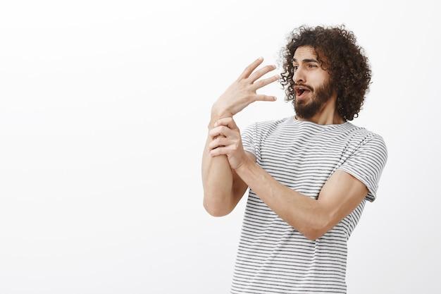 Iemand die zijn arm bedient. grappige speelse knappe man met krullend haar, naar achteren buigend en schreeuwend terwijl ze lol hebben, kinderachtig zijn