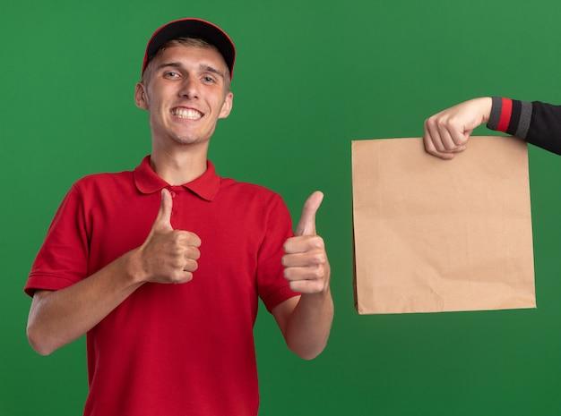 Iemand geeft een papieren pakket aan een lachende jonge blonde bezorger die met twee handen omhoog duimt