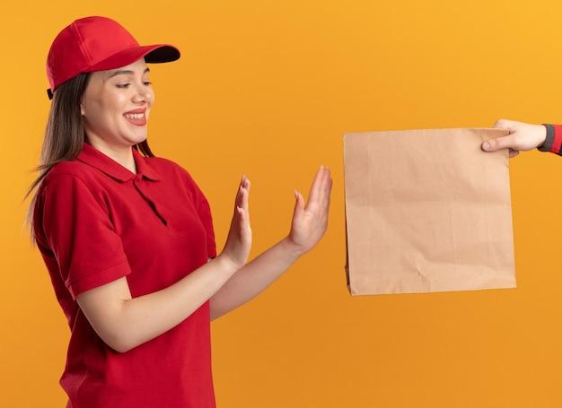 Iemand geeft een papieren pakket aan een tevreden mooie bezorger in uniform, hand in hand open gebaren zonder teken geïsoleerd op oranje muur met kopie ruimte