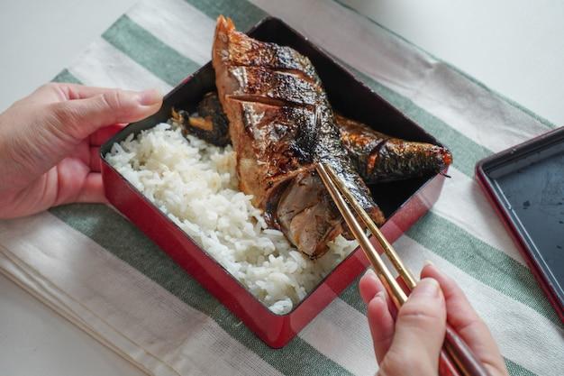 Iemand hand met behulp van stokjes proberen een gegrilde saba of makreel vis te plukken geserveerd met gekookte rijst in vierkante bento box op wit en groen gestreepte placemat op witte tafel