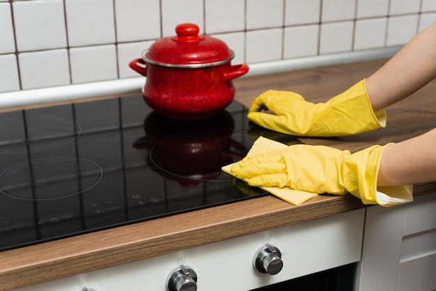 Iemand is een fornuis aan het wassen in gele handschoenen. iemand maakt een keuken schoon met een lap.
