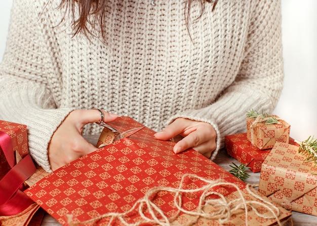 Iemand knipt ambachtelijk papier en cadeautjes inpakken op houten tafel close-up