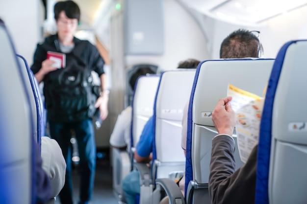 Iemand leest het menu op de stoel in het vliegtuig en staat klaar om de stewardess te bestellen.