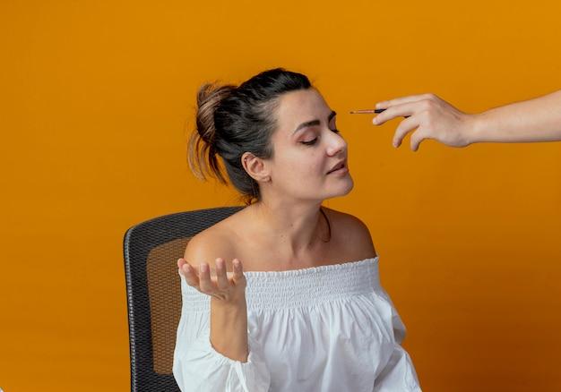 Iemand oogschaduw met make-up borstel toe te passen op ogen van blij mooi meisje zittend aan tafel met make-up tools geïsoleerd op oranje muur