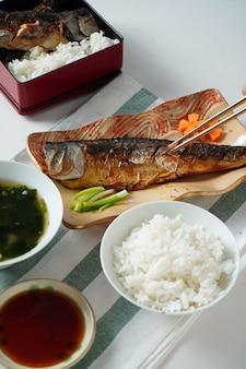 Iemand overhandigt stokjes en probeert een gegrilde saba of makreelvis te plukken geserveerd met misosoep en gekookte rijst op witte en groene gestreepte placemat op witte tafel