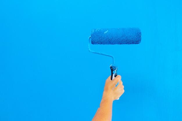 Iemand schildert muur in een blauwe kleur