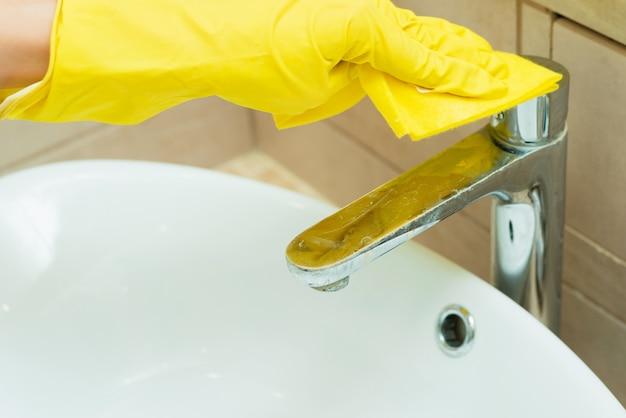 Iemand wast een gootsteen in gele handschoenen. iemand maakt een badkamer schoon met wasmiddelen