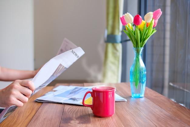 Iemand zet hete koffie op tafel terwijl hij de krant leest.