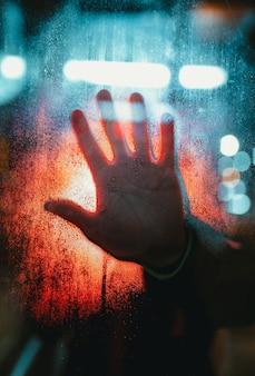 Iemands hand aanraken van een glas bedekt met regendruppels met bokeh lichten