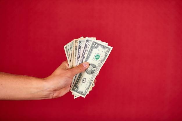 Iemands hand die en dollarsbankbiljetgeld houdt toont dat op rode achtergrond, binnen, studioschot, exemplaarruimte wordt geïsoleerd