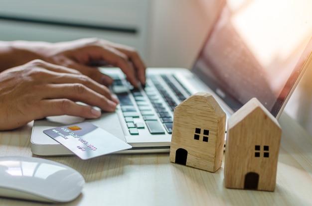 Iemands hand die informatie over zaken, creditcard en woningkrediet zoekt met een laptop computer aan zijn bureau