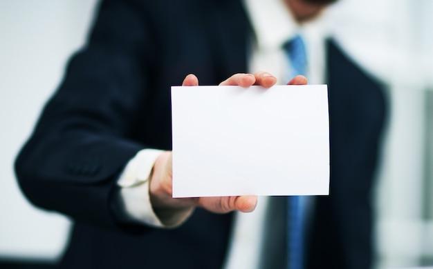 Iemands hand die visitekaartje toont - close-up die op grijze achtergrond is ontsproten