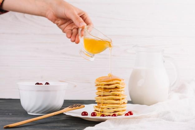 Iemands hand gieten honing over de heerlijke pannenkoeken op houten tafel