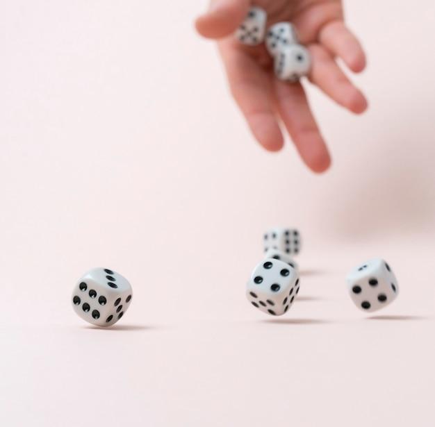 Iemands hand gooit de dobbelstenen kubussen op tafel, win gokcasino Premium Foto