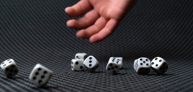 Iemands hand gooit de dobbelstenen kubussen op tafel, win gokcasino