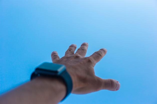 Iemands hand met een elektronische klok reikt naar de blauwe lucht.