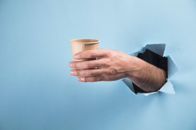 Iemands hand met een glas op een blauwe scène