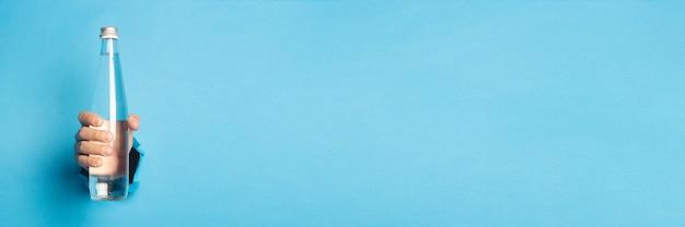Iemands hand met een glazen fles met water op een heldere blauwe achtergrond