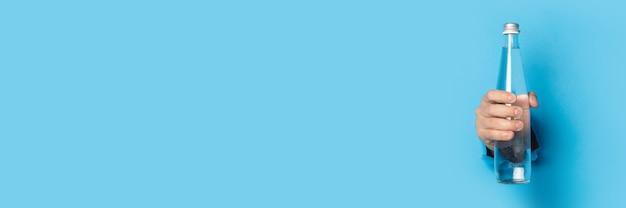 Iemands hand met een glazen waterfles met het deksel gesloten op een blauwe achtergrond