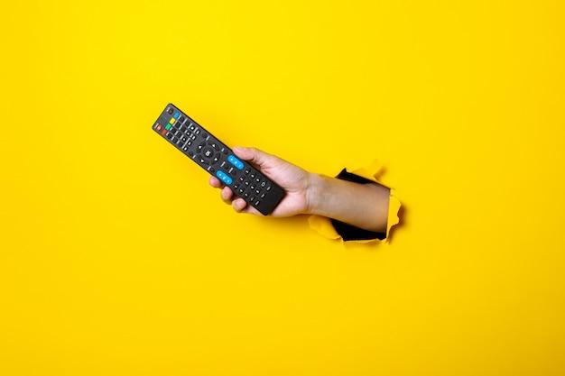 Iemands hand met een tv-afstandsbediening op een heldere gele achtergrond