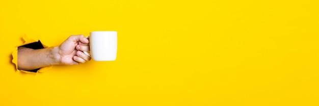 Iemands hand met een witte kop op een heldere gele achtergrond