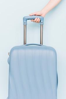 Iemands hand met handvat van reisbagage tegen blauwe achtergrond