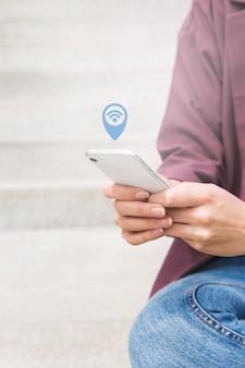 Iemands hand met mobiele telefoon op zoek naar wi-fi verbinding