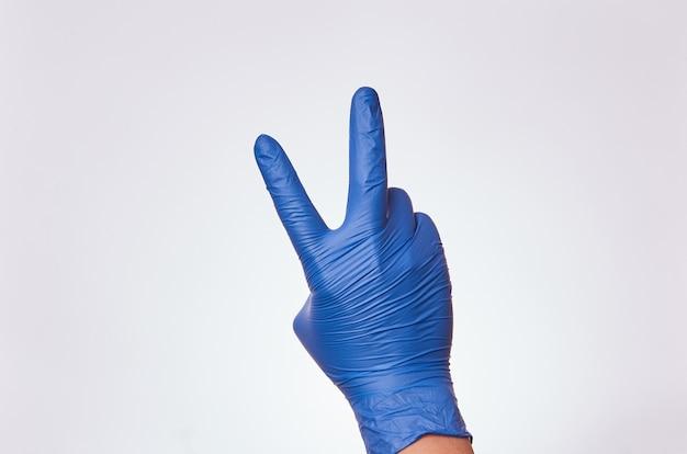 Iemands hand met nitrilhandschoenen voor medicijnen die een gebaar van vrede en liefde maken