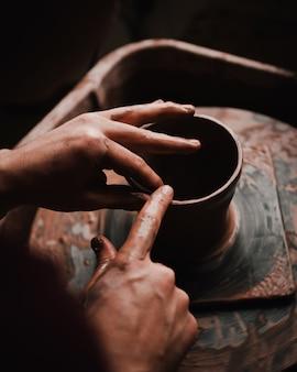 Iemands handen en vingers die een kleipot vervaardigen