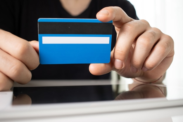 Iemands handen met een blauwe creditcard over een reflecterend oppervlak in een witte kamer