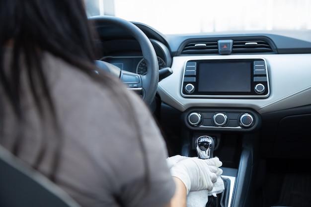 Iemands handen met handschoenen die binnen een auto schoonmaken