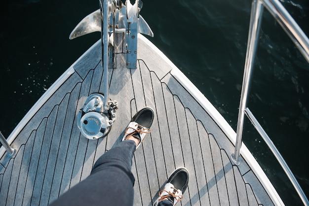Iemands voeten op de boot die overdag op zee vaart