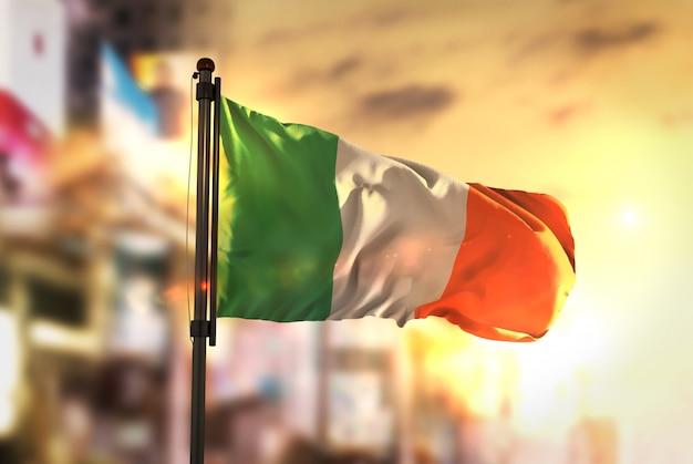 Ierland vlag tegen stad wazige achtergrond bij zonsopgang achtergrondverlichting