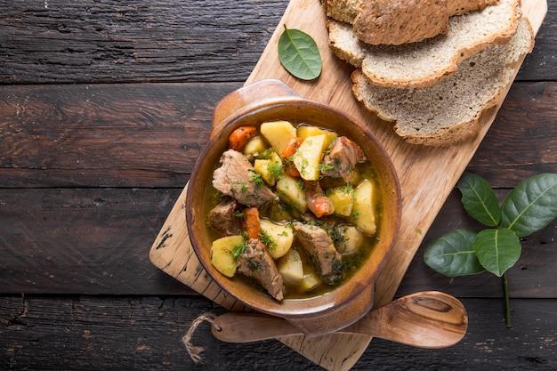 Iers diner. rundvlees gestoofd met aardappelen, wortelen en sodabrood op houten tafel, bovenaanzicht, kopie ruimte. zelfgemaakt wintercomfortvoedsel - langzaam gekookt