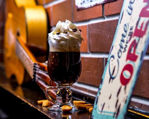 Ierse koffie met slagroom versierd met chocoladeschilfers op bakstenen muur