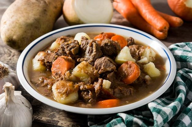 Ierse rundvleeshutspot met wortelen en aardappels op houten lijst
