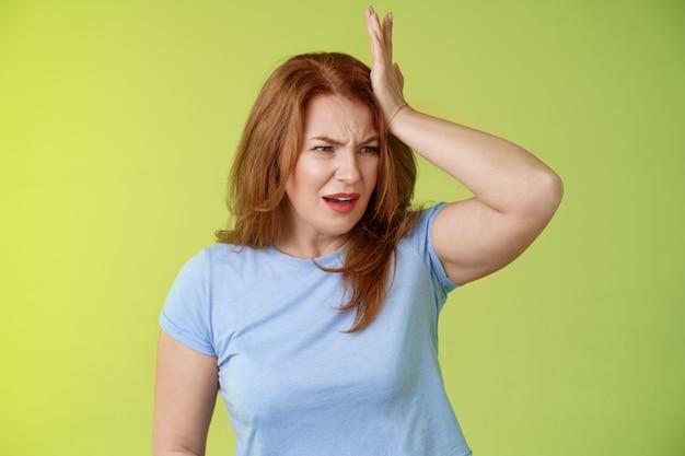 Iets belangrijks misstap mijn geest bezorgd bezorgd boos roodharige rijpe vrouw stomp voorhoofd wegdraaien gefrustreerd fronsend teleurgesteld vergeten afspraak afzeggen staan groene muur
