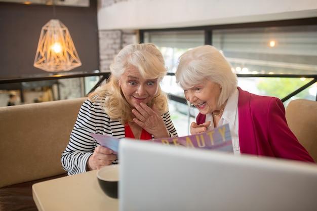 Iets interessants. knappe bejaarde dames die achter de laptop zitten en geïnteresseerd kijken