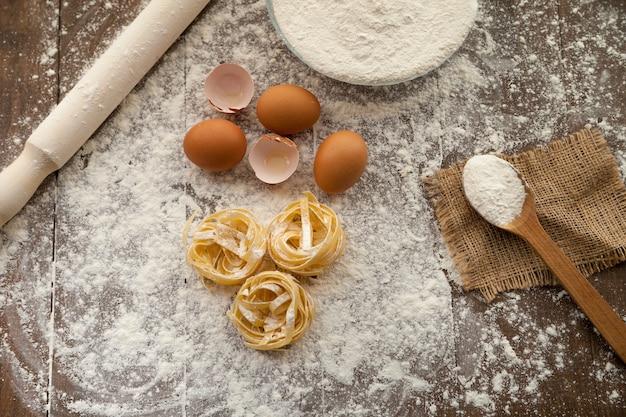 Iets lekkers koken met eieren, meel en fettuccine met keukenhulp. uitzicht van boven.