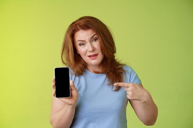Iets vragen ondervraagd ernstig uitziende ontevreden roodharige rijpe moeder acteren boos vasthouden smartphone wijzend blanco gsm-scherm vraag antwoorden gevonden dochter socialmedia foto's