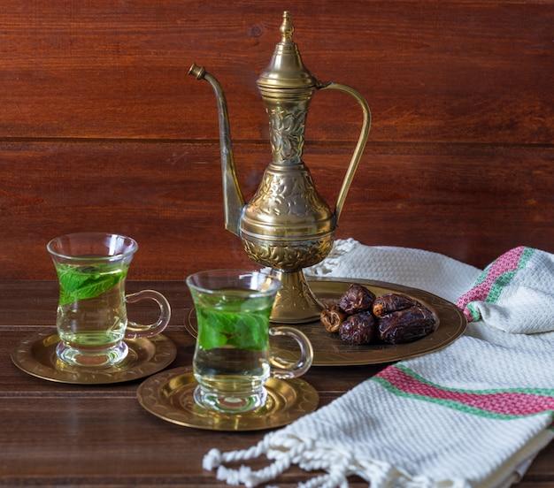 Iftar en suhoor ramadan-concept, mentha thee op glazen kopjes en dadels met een oude theepot