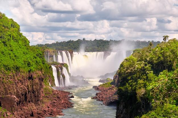 Iguazu-watervallen in argentinië. toeristische motorboten gaan richting krachtige watercascade en creëren mist over de iguazu-rivier. weelderig loof van subtropisch regenwoud langs rode stenen oevers ..