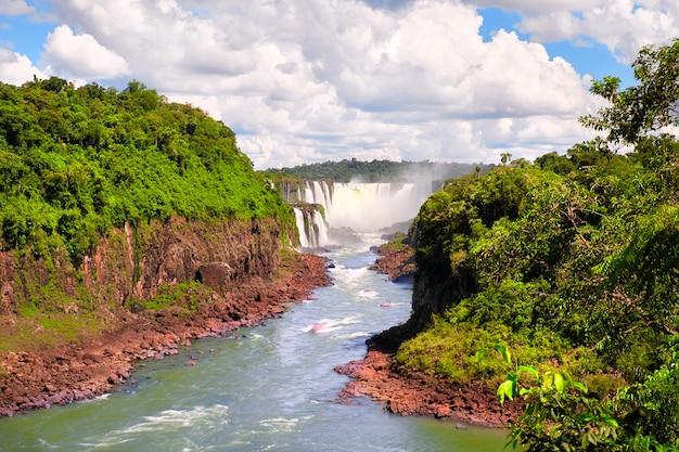 Iguazu-watervallen in argentinië. toeristische motorboten gaan richting krachtige watercascade en maken mist over de iguazu-rivier. weelderig loof van subtropisch regenwoud langs rode stenen oevers.