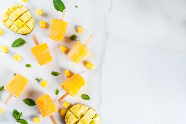 Ijs, ijslollys. biologisch dieetvoeding, desserts. bevroren mango smoothie, met muntblaadjes en vers mangofruit, op een witte marmeren tafel. copyspace bovenaanzicht