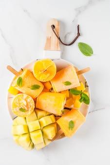 Ijs, ijslollys. biologisch dieetvoeding, desserts. bevroren mango smoothie, met muntblaadjes en vers mangofruit, op plaat, op witte marmeren tafel. bovenaanzicht