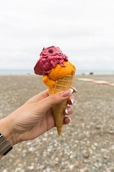 Ijs in een wafelbeker in de hand van een meisje op het strand van batumi. hoge kwaliteit foto