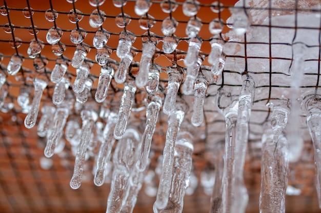 Ijs op het rooster gevormd na een ijzige regen met ijspegels na ijzel