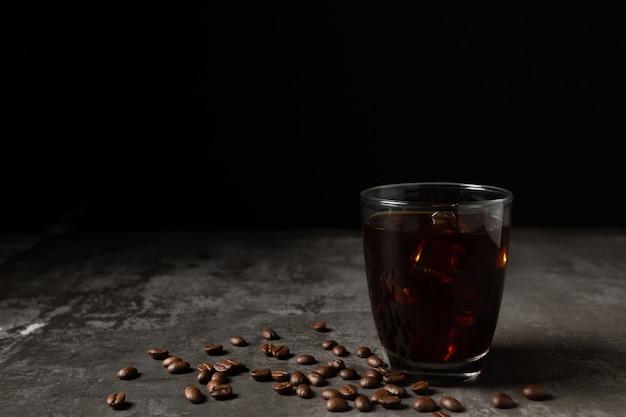 Ijs zwarte koffie in een glas op de houten tafel.